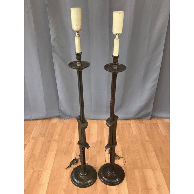 An uncommon pair of early 1940s mahogany candlestick-style adjustable height floor lamps by renowned California designer...