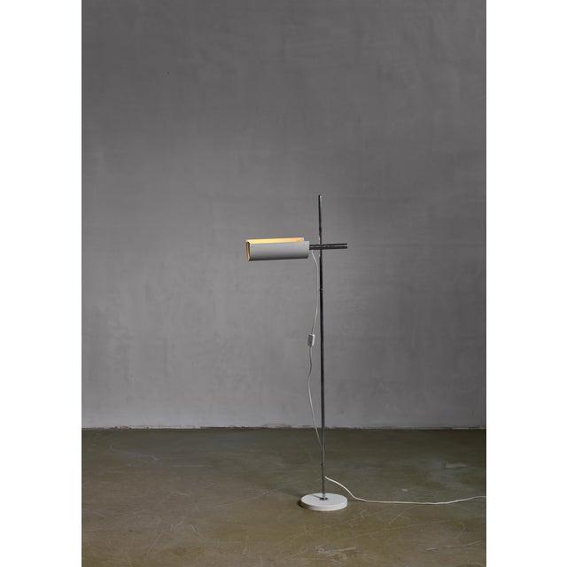 An adjustable floor lamp designed by Ben af Schultén for Artek. The lamp has a height-adjustable and swiveling white...