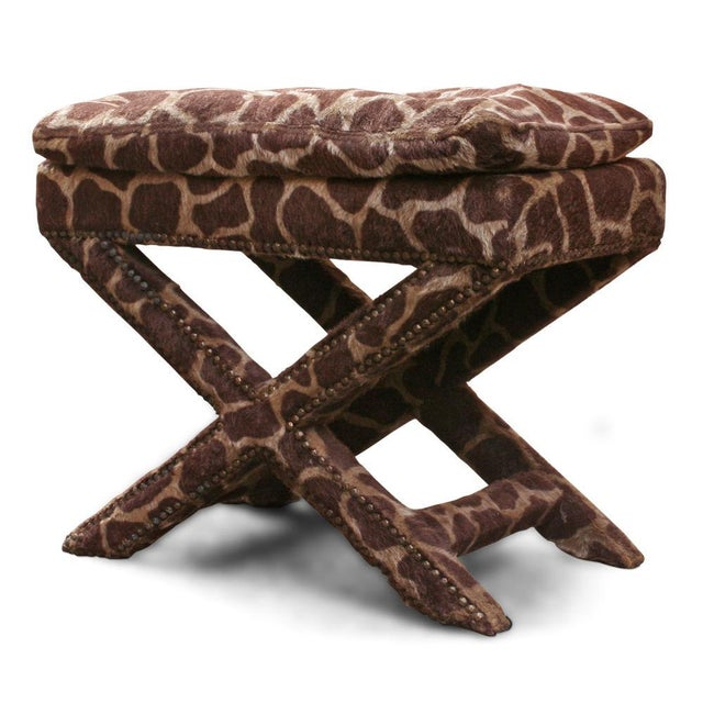 A fully upholstered X-frame bench in giraffe print pony skin with exposed nail head details to the base. After Billy...