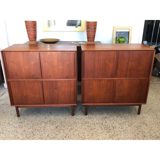 A great pair of solid teak cabinets with sliding doors and adjustable shelves inside. Finger- jointed case on round legs....