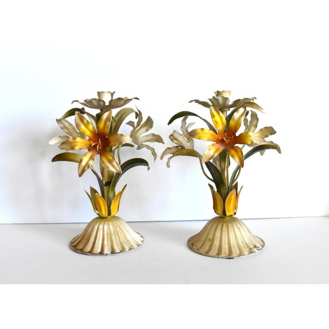 A pair of vintage Italian painted tole (toleware) candlesticks or candle holders, with three yellow lilies on each.