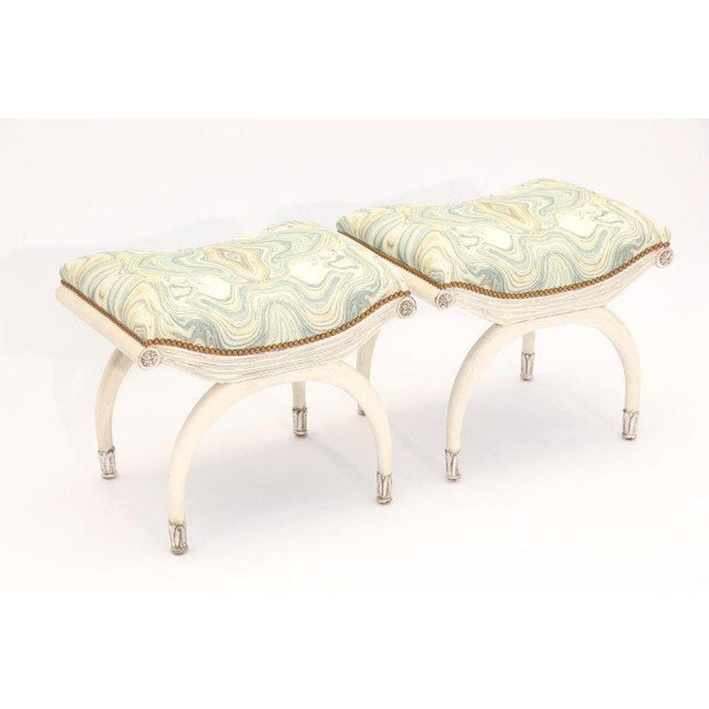 Pair of benches, each having a padded, rectangular seat, upholstered with nailheads, on painted frame with parcel silver...