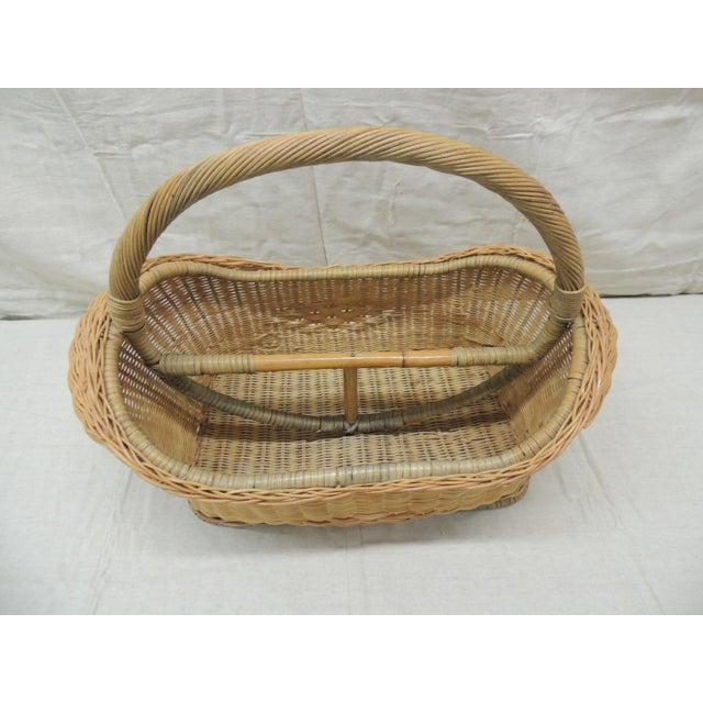 """Vintage wicker magazine rack with handles. Organic bulbous shape with a middle divider Handwoven in Indonesia Size: 21""""W x..."""
