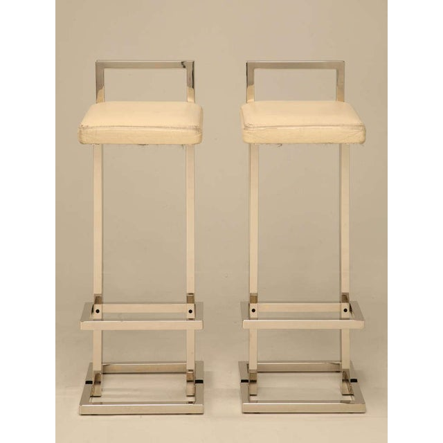 Circa 1970, Chrome mid-century modern bar stools, with their creme leather seats by Romeo Rega. The pair is completely...