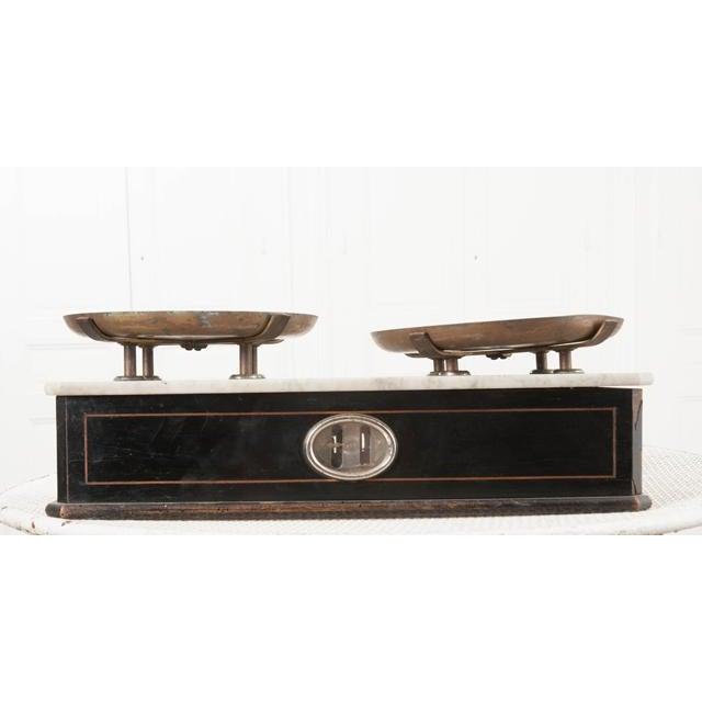 An antique French counter or grocer scale in ebonized hardwood and mahogany inlay with white marble top, circa 1880. The...