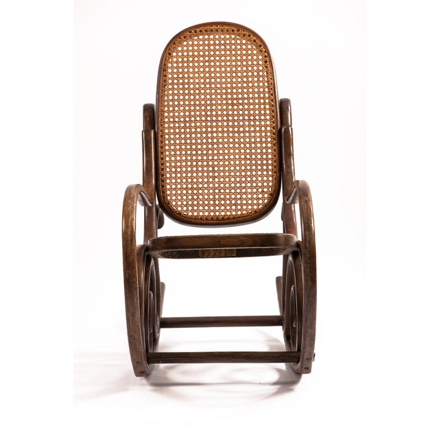 A children's bentwood rocking chair in a natural stain with rattan seat and back. By Marchio Di Fabbrica Depositato....