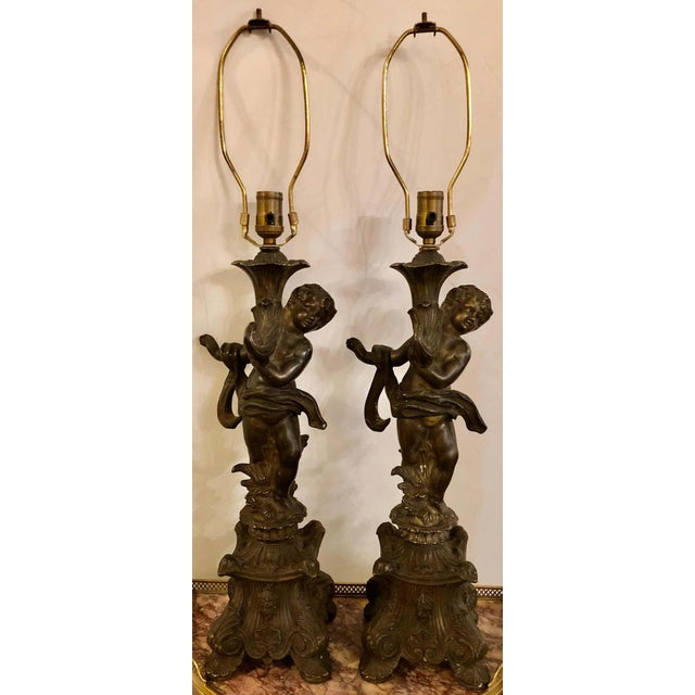 Pair of bronze patinated putti table lamps each in the Louis XVI manner holding up a cornucopia on top of a pedestal base....