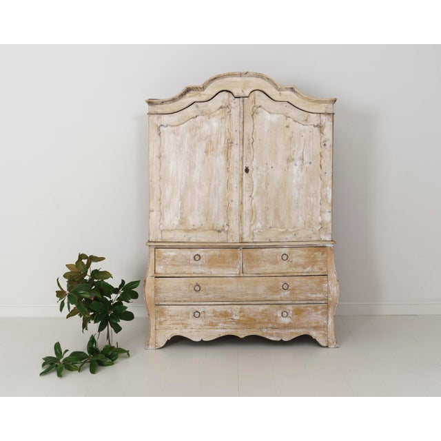 A hand-carved, two-part French linen press with traces of old white wax polish from the 19th century. This cabinet is...