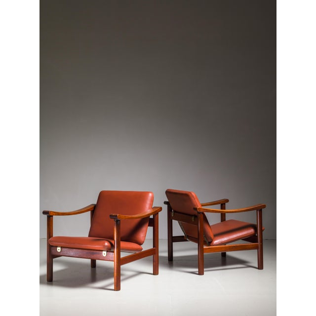 A pair of rare Hans Wegner lounge chairs for GETAMA. The chairs are made of a wooden frame, with a reclining seat and...