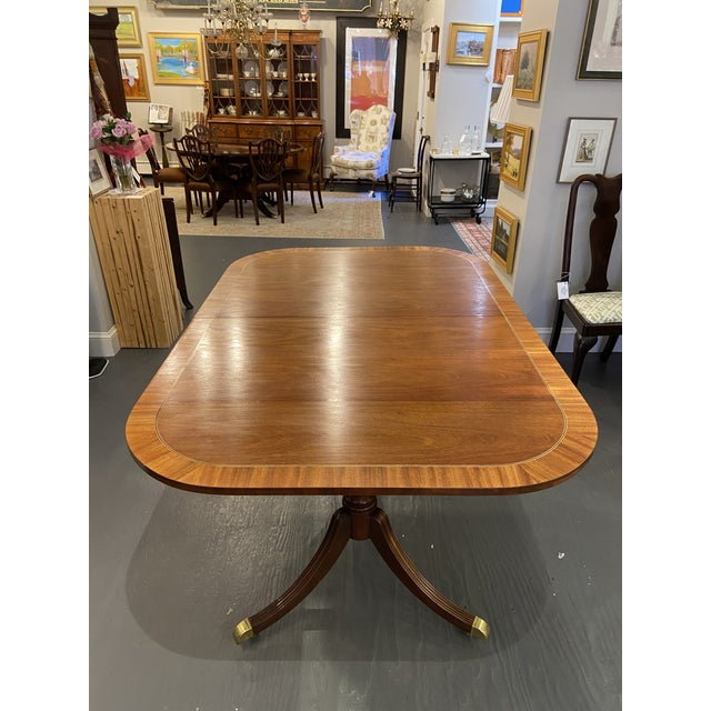 This is a mahogany with a satin and ebony banding inlay. It is a double pedestal base. The feet are brass with castors. It...