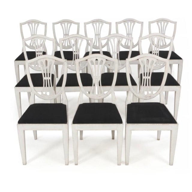 Sweden, c. 1930. A set of 12 white painted Gustavian dining chairs, carved open work back rests, straight legs, black...