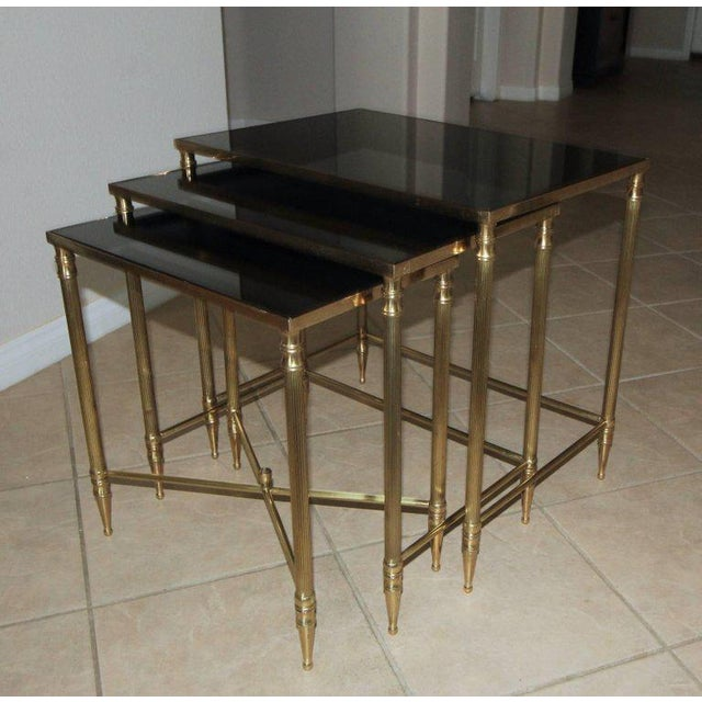 "Trio of French brass nesting tables with newer dark graphite colour mirrored glass inset tops. Measures: Table #1 - 22"" L..."