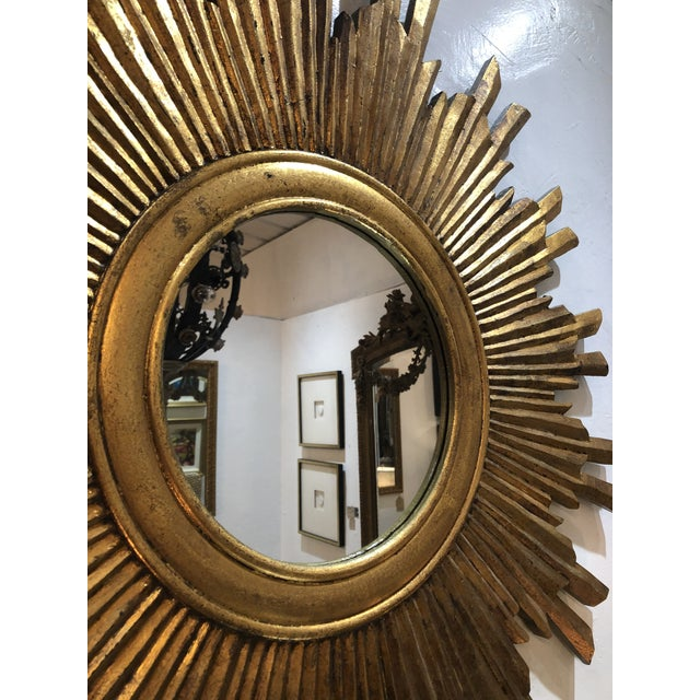 """A large gilt wood mirror. This piece measures 35 inches across its longest point. """"Traditionally, the """"sunburst"""" mirror..."""