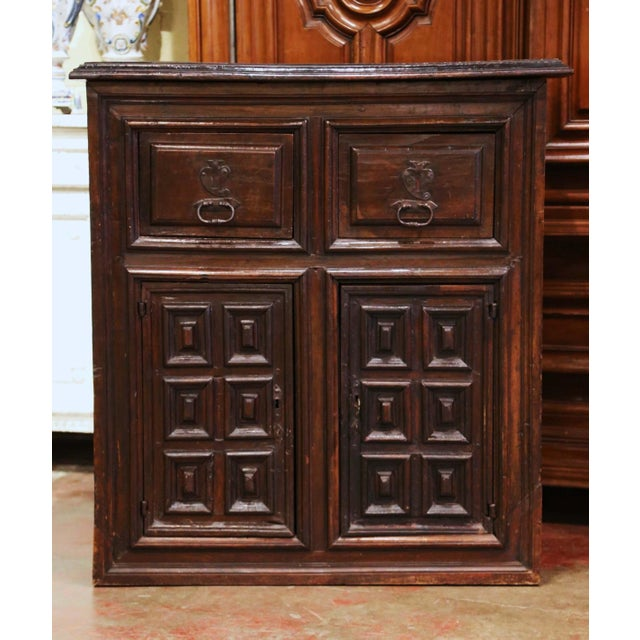 Hand carved in northern Spain circa 1700, the fruit wood cabinet features two drawers across the front dressed with the...