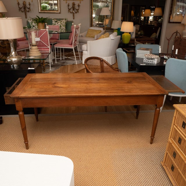 A nice looking farm table in cherry with tapered legs, featuring a drawer on one end and a pull-out tray on the other end....