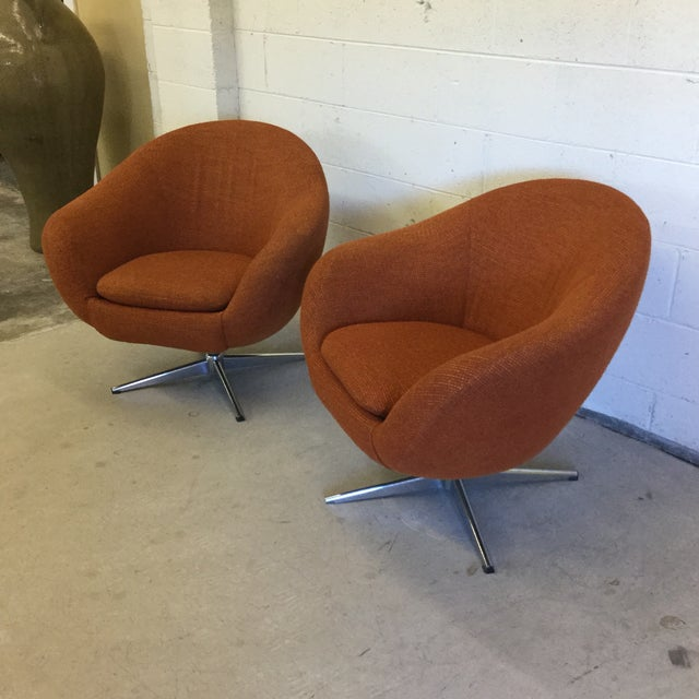 Great orange woolish upholstery on molded barrel shape rests atop a chrome 4 prong base that swivels. Very clean. One of...