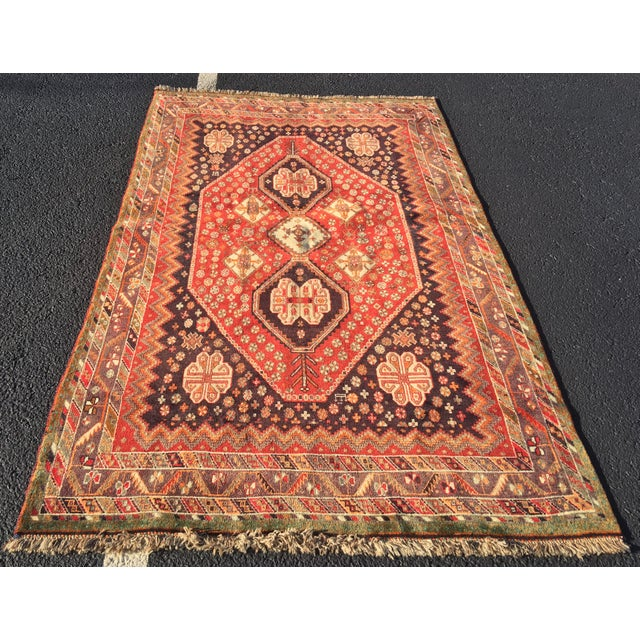 This is an old vintage Persian Qashqai area rug in red, plum, and several other vibrant hues.