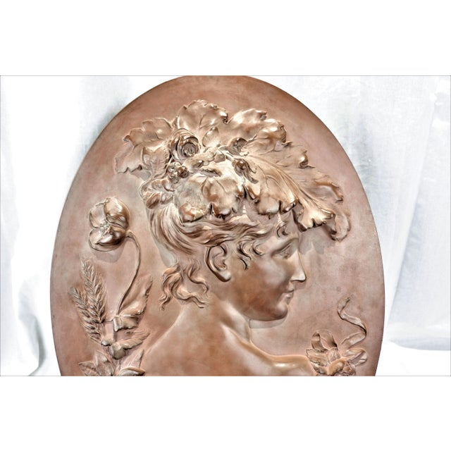 A large hand sculptured terracotta plaque of a Victorian woman's profile with flower adornments. Plaque has a thick...