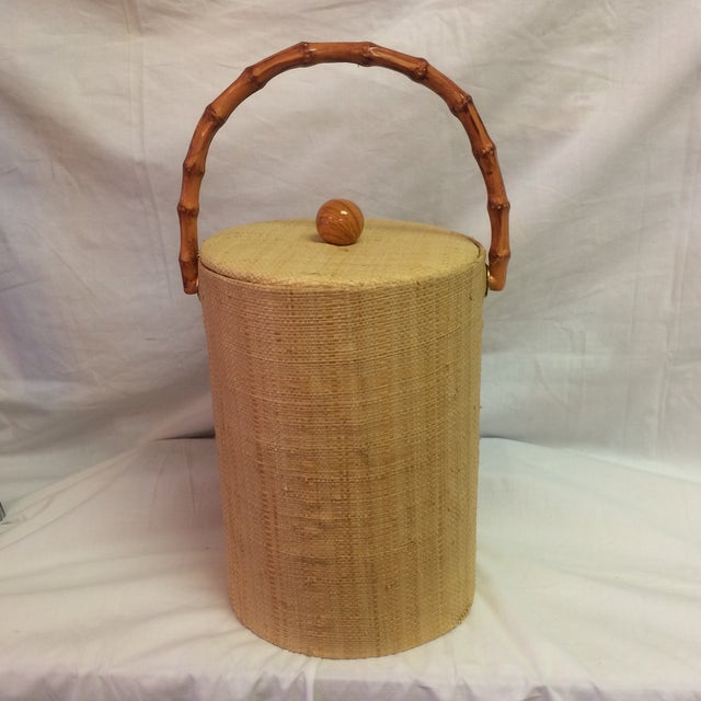 Vintage grass cloth rattan handled ice bucket with plastic lining.