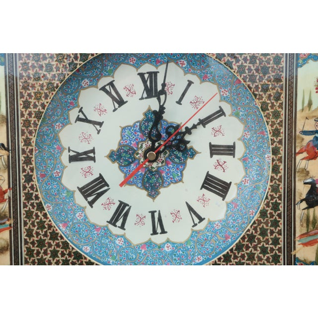 This Persian Khatam Kari clock is hand painted with several hunting scenes, and features a blue & white floral clock face...