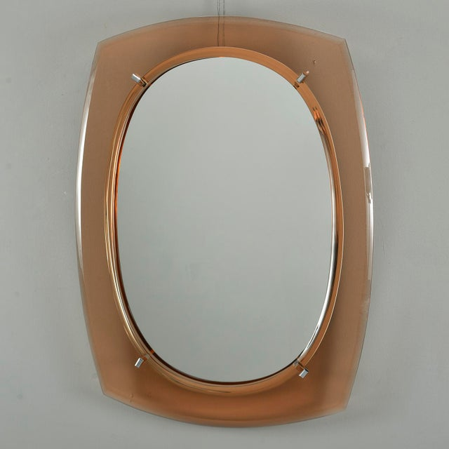 Circa 1960s mirror by Italian maker Cristal Arte features an oval mirror with a pale coral rounded corner rectangular art...
