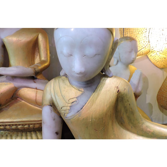 This golden glowing alabaster inwa from Burma sits with a group of alabaster spirits.