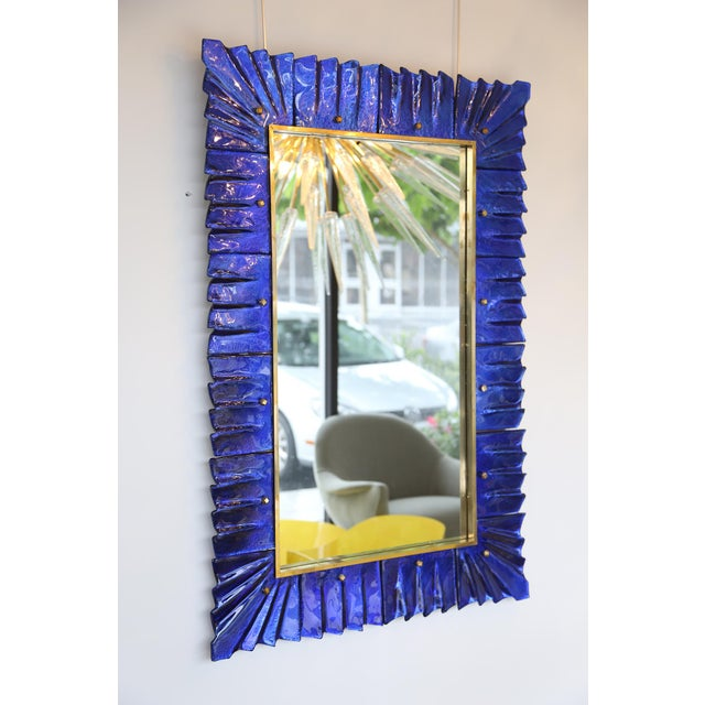 Spectacular studio built cobalt blue glass mirror with brass accents. The rectangular mirror plate is surrounded with...