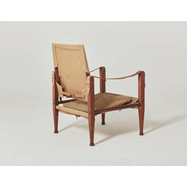 A Kaare Klint safari chair, made by Rud Rasmussen, Denmark. Original faded khaki canvas and ashwood. Complimentary...