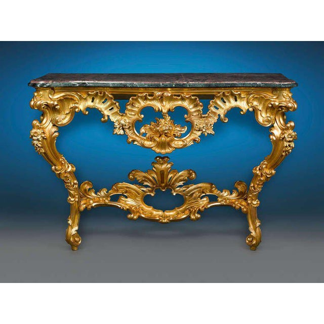This outstanding Louis XV-period giltwood console table is lavishly carved with the naturalistic, voluptuous motifs. The...