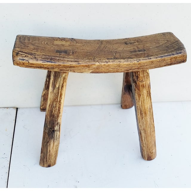 Petite 4-legged Chinese stool made of elm wood with a sloped saddle seat ca1910. Sturdy and in excellent condition, used...