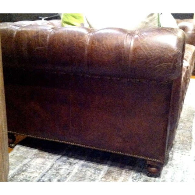 One pair of monumental distressed leather chesterfield sofas.