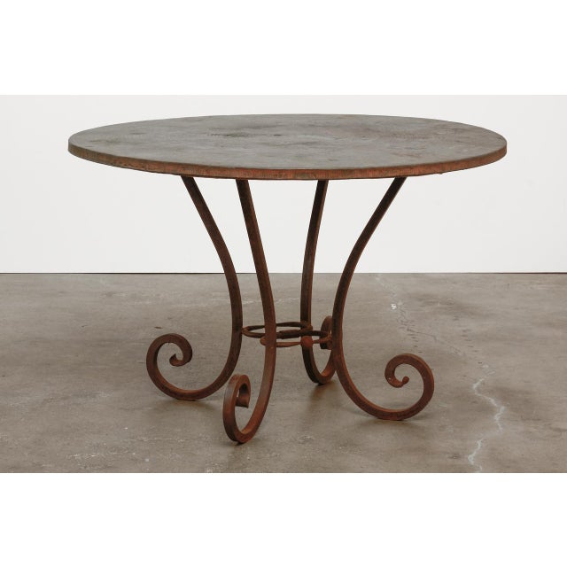 Dramatic scrolled wrought iron dining table featuring a hammered copper top. The copper top showcases a hand-hammered...