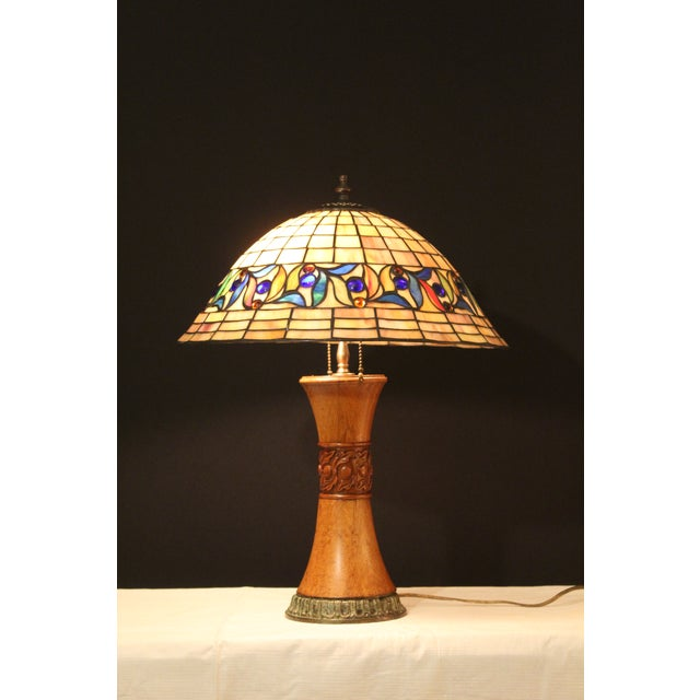 Beautiful detailing in this unusual table lamp. Handmade shade, as well hand turned and carved base. Consisting f hand cut...