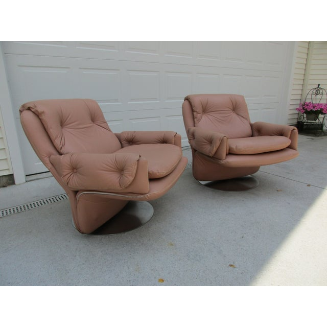 Here's an amazing pair of tufted mid-century modern swivel lounge chairs on a cantilever frame. The chairs swivel on a...