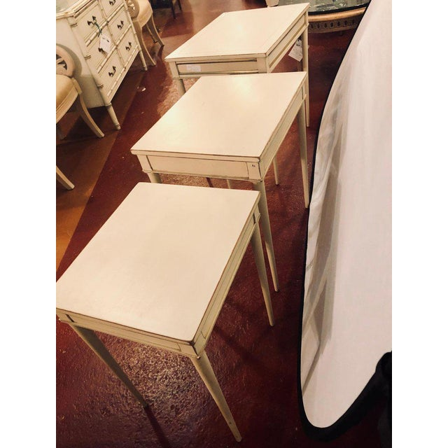 Set of three white painted nesting / stacking tables attributed to Jansen. These Hollywood Regency style gilt and paint...