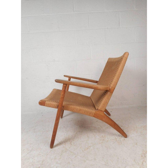 This beautiful Danish modern lounge chair features a solid oak frame with angled back legs and sculpted arm rests. Sleek...