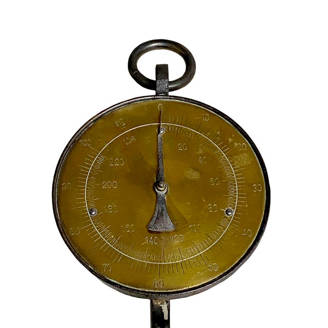 A heavy 19th century European brass hanging scale with cast iron hook for measuring up to 100 kg and 220 lbs.