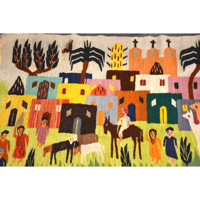 A vibrant color all wool handmade Kilim rug with a beautiful village scene with animals and people.