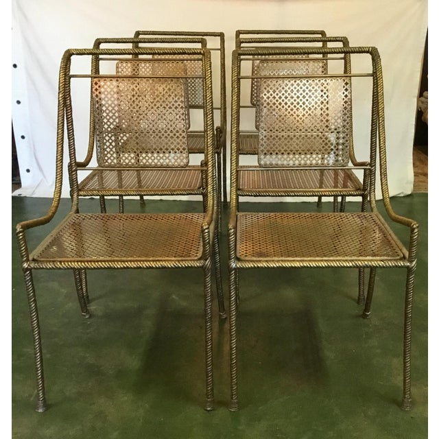 This set of metal chairs are shown in striking gold. The back and seats have an alternating pierce-work detail of circles...