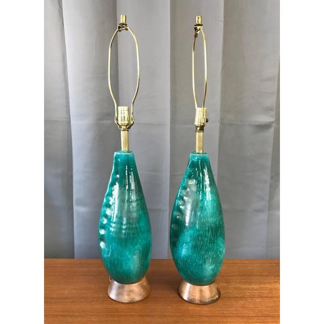 A pair of Mid-Century turquoise ceramic table lamps with wood bases by Marcello Fantoni, circa 1950s Design slyly...