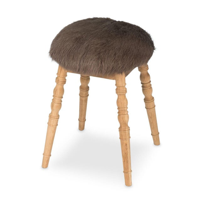 Estimated Retail Price: $594. The 'Winoma' stool is made from wood and is upholstered in a brown goatskin rug. Features a...