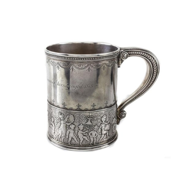 A charming Tiffany & Co. sterling silver child's cup, circa 1875. Beautiful hand chased details, with a marching band to...
