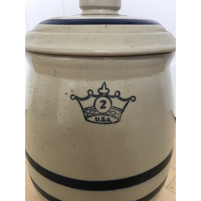 Listed is a stoneware drink dispenser. The front is marked with the Crown & royal blue stripes. This piece features an...