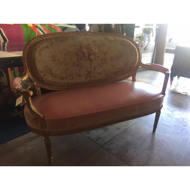 This is a French settee from the early 20th century. The piece features finely carved gilt wood and a leather seat.
