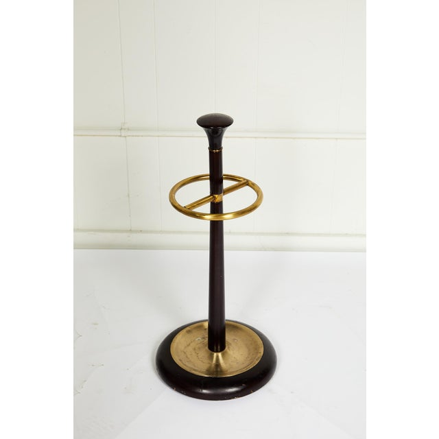 20th century umbrella or walking stick stand with a mahogany stained base and shaft ornamented with brass fittings and a...