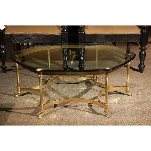Sculptural beveled 3/4 thick beveled glass table on high quality polished gilt brass stand with six brass legs terminate...