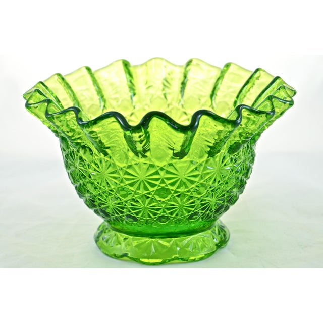 Bright green bowl with a ruffled and crimped rim as well as a daisy and button pattern. No maker's mark. Light wear.
