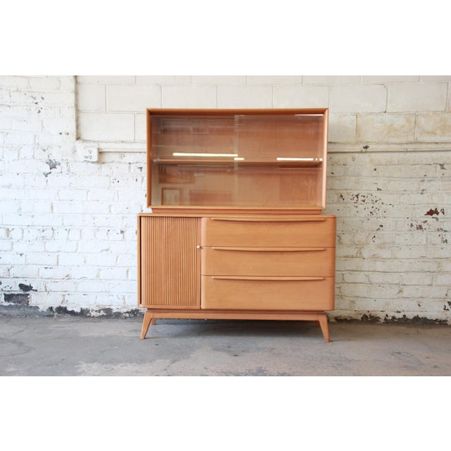 Offering a very nice Heywood-Wakefield sideboard with glass-front hutch top. The piece has a tambour door on the left side...