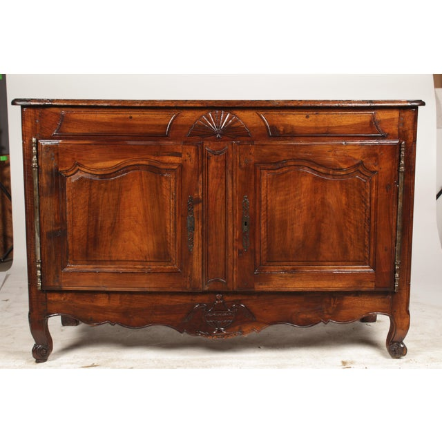 Antique French credenza in the Louis XV-Style featuring walnut construction, double paneled doors with carved fan above...