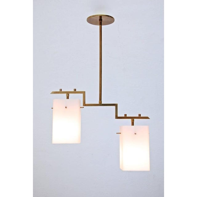 Beautiful geometric pendant from Italy with two cubic glass shades and patina brass hardware. Candelabra sockets. Total...